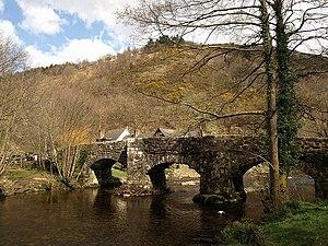 Fingle Bridge - Fingle bridge viewed from upstream, with the site of Prestonbury Castle behind