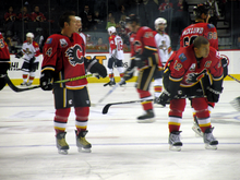 A player in full uniform but without a helmet stands to the right of a teammate who is crouched over. Both players are looking to their left as several others skate in the background.