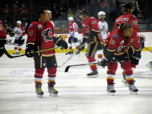 Theoren Fleury -  alt=A player in full uniform but without a helmet stands to the right of a teammate who is crouched over. Both players are looking to their left as several others skate in the background.