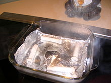 Aluminum Foil In A Square Pyrex Dish Of Water With Tear Where The