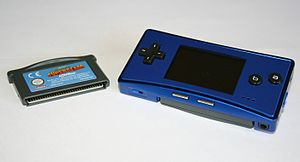 Game Boy Micro - A blue Game Boy Micro next to a Game Boy Advance cartridge.