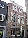 foto van Huis met in blokken gepleisterde ingezwenkte lijstgevel. Staafankers. Winkelpui uit plm 1890
