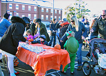 Children receiving small treats from a table with a shiny orange covering and two small pumpkins on it. One child to the right is in costume as a green turtle. There are adults behind them wearing heavy coats and hats. In the rear is a large brick building with snow on the roof