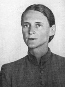 A grainy black-and-white photograph of a woman with hair tightly drawn about her hair wearing a shirt with a high collar and buttons