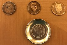Three coppery coins grouped with a silver one, the last mounted in a dish. They are all Kalākaua dollars by design.