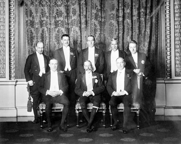 King George V with his prime ministers. Standing (left to right): W.S. Monroe (Newfoundland), Gordon Coates (New Zealand), Stanley Bruce (Australia), J. B. M. Hertzog (Union of South Africa), W. T. Cosgrave (Irish Free State). Seated: Stanley Baldwin (United Kingdom), William Mackenzie King (Canada).