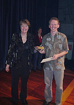 Jan Wright presenting a trophy to Axel Wilke, Axel holding a certificate