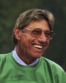 Joe Namath wearing glasses and a green shirt.