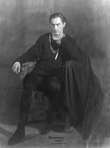 Barrymore, cleanshaven, in an all-black costume as a brooding Hamlet, sitting on a chair, looking slightly to his right of the camera