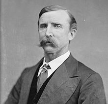 A man with short, dark hair and a mustache wearing a dark jacket and vest, patterned tie, and white shirt