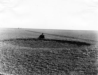 Great Plains - The Great Plains before the native grasses were ploughed under, Haskell County, Kansas, 1897, showing a man sitting behind a buffalo wallow.