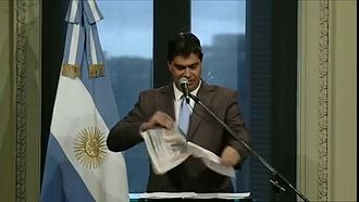 Conflict between Kirchnerism and the media - Jorge Capitanich destroying a Clarín newspaper after accusing the newspaper of publishing false information.