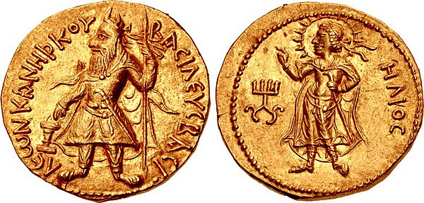 "Early gold coin of Kanishka I with Greek language legend and Hellenistic divinity Helios. (c. 120 AD). Obverse: Kanishka standing, clad in heavy Kushan coat and long boots, flames emanating from shoulders, holding a standard in his left hand, and making a sacrifice over an altar. Greek legend: BASILEUS BASILEON KANE[?]KOU Basileus Basileon Kanishkoy ""[Coin] of Kanishka, king of kings"". Reverse: Standing Helios in Hellenistic style, forming a benediction gesture with the right hand. Legend in Greek script: ELIOS Helios. Kanishka monogram (tamgha) to the left. Kanishka I Greek legend and Helios.jpg"