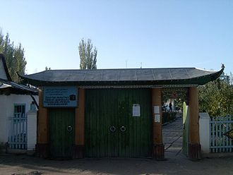 Dungan people - The gate of the Dungan Mosque in Karakol, Kyrgyzstan. The upper text on the sign is a partially Uyghurized rendering of the mosque's Kyrgyz name into the Uyghur Arabic alphabet: Isiq-köl oblasttiq Qaraqol sharindaghi Ibrahim Haji atindaghi borborduq mäsjid. The lower text is Kyrgyz in the Cyrillic script: Ysyk-Köl oblasttyk Karakol shaaryndagy Ibrakhim Ajy atyndagy borborduk mechit—Central Mosque in the name of Ibrahim Hajji in the city of Karakol, oblast of Ysyk-Köl.