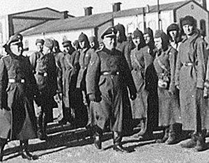 Trawniki men - Inspection of Trawnikimänner (some of them, still wearing Soviet Budionovkas) by SS-Hauptsturmführer  Karl Streibel (smiling) at the SS Trawniki training division. As Hiwis, they were tasked with the liquidation of the Jewish Nazi-era ghettos in occupied Poland