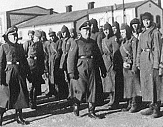 Trawniki men - Inspection of Trawnikimänner (some of them, still wearing Soviet Budionovkas) by SS-Hauptsturmführer  Karl Streibel (smiling) at the SS Trawniki training division. As Hiwis, they were tasked with liquidating Nazi-era Jewish ghettos in occupied Poland