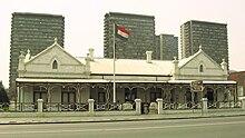 Et hollandsk hus i kolonistil med Den Sydafrikanske Republiks flag, der flyver udenfor.