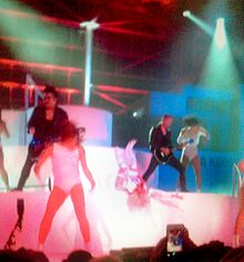 Guitarists in black and dancers in white dress perform on a white stage, bathed in red and blue lights.
