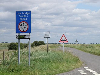 Metrication of British transport - A road sign warning of a low bridge with its distance given in imperial units and its height given in dual imperial/metric units