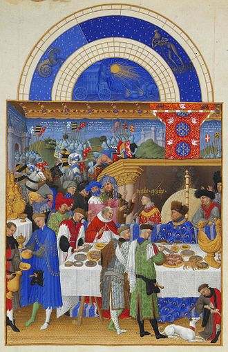 Medieval cuisine - John, Duke of Berry enjoying a grand meal. The Duke is sitting at the high table in front of the fireplace, tended to by several servants including a carver. On the table to the left of the Duke is a golden salt cellar, or nef, in the shape of a ship; Très Riches Heures du Duc de Berry, ca 1410.