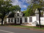 A short distance from the railway station at the corner which Dorp Street forms with Somerset West Road, stands the first remarkable old house in this street. It is called Libertas Parva or Little Libertas and it is on the right side of the street (now Rembrandt van Rijn Art Centre). The oldest feature of the house is its four side gables; they are of the holbol type, but show a breaking up of the concaves and convexes into wavy lines reminiscent of a similar tendency in the front gables of the Zevenrivieren-Hazendal type, c, 1790. The house may therefore date from 1783 or soon after. Philip Jacob Haupt purchased the farm in 1819 and it must be accepted that he was responsible for the erection of the present front gable, with almost straight outlines, with the two front doors built in and also for the Georgian windows. Their outer surrounding pilasters are continued upward to form the outer gable pilasters. The Libertas Parva building complex is a fine example of the Stellenbosch architecture in the 18th and 19th centuries and lends a particular character to that part of the village. As the home of well-known Stellenbosch families it is also of great historic value.