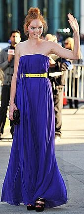 Cole outside wearing a strapless purple dress with her hair up in a large bun, surrounded by photographers.