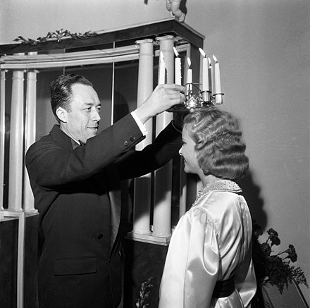 Camus crowning Stockholm's Lucia on 13 December 1957, three days after accepting the Nobel Prize in Literature Lucia 1957.jpg