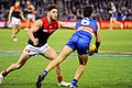 Luke Dahlhaus handballing away from Tomas Bugg.jpg