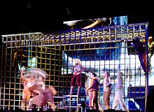 A giant cage, in front of which are gathered a number of people. Among them, a blond woman in brown jacket, pants and boots, stands on top of one of the rods and watches two men dancing.