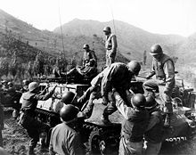 A group of soldiers are surrounding a tracked vehicle that carries two injured soldiers. One of the injured is getting off with the help of two soldiers while another is lying on top of the vehicle.