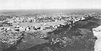 Black-and-white photograph of a city in the desert showing a basaltic ridge on the right and a skyline with numerous buildings among which is a domed mosque with two minarets