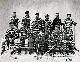 "A group photograph of ten hockey players wearing horizontally striped jerseys with a maple leaf logo surrounding the letters ""CAC"", along with their coach"