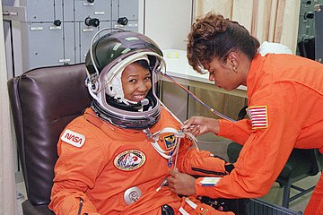 NASA astronaut Mae Jemison waits as her suit technician, Sharon McDougle, performs a unpressurized and pressurized leak check on her spacesuit.jpg