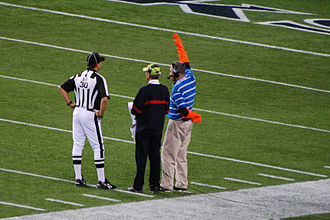 National Football League on television - The network television coordinator with orange sleeves will lower his arm when the commercial is over.