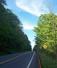 "A two-lane road in a wooded area where one side of the road has a steep slope. A ""Fallen Rock Zone"" sign is visible on the right of the road"