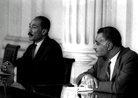 Two men in suits seated next to each other with their arms resting on a table
