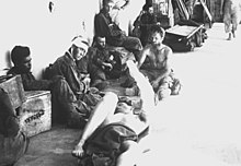 Several men are sitting and laying down near a building. Some are bandaged, and others have no shirts. Various boxes and cots are nearby.