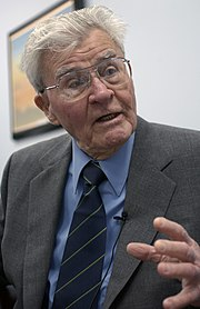 A grey-haired man wearing glasses, in a grey suit with blue shirt and tie.