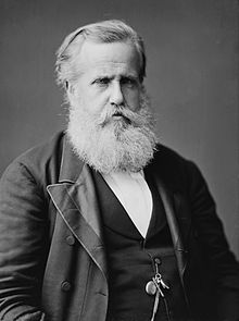 Hauf-length photographic portrait o an aulder man wi white hair an beard dressed in a dark jacket an necktie