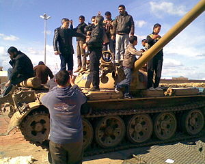 Timeline of the 2011 Libyan Civil War - Demonstrators on an abandoned T-54/55 tank during a rally in Benghazi