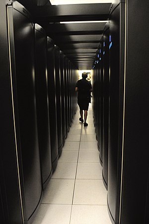 Supercomputer architecture - A person walking between the racks of a Cray XE6 supercomputer