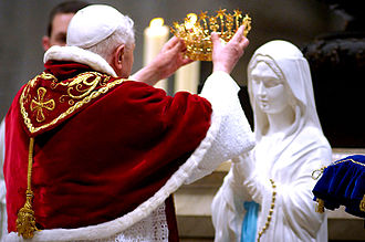 Canonical coronation - Pope Benedict XVI placing a Fleur-de-Lys styled crown on a statue of Our Lady of Lourdes, although this novelty event was not a rite of canonical coronation. During a Plenary indulgence for the World Day of the Sick, 11 February 2007.