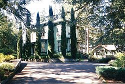 Photograph of a large house partially obscured by trees