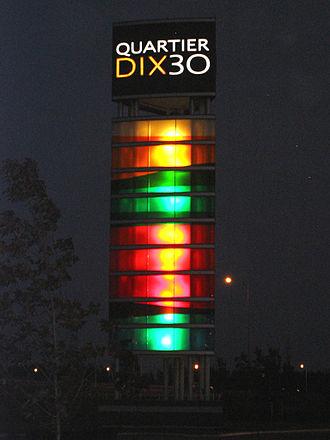 Quartier DIX30 - The Quartier DIX30 tower, illuminated at night.