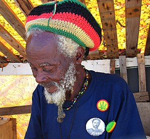 Rastafari - Rastaman in Barbados, wearing the Rastafari colours of green, gold, red and black on a rastacap.