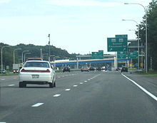 Ground-level view of four lanes of a busy freeway; several green exit signs and two overpass bridges are visible in the distance.