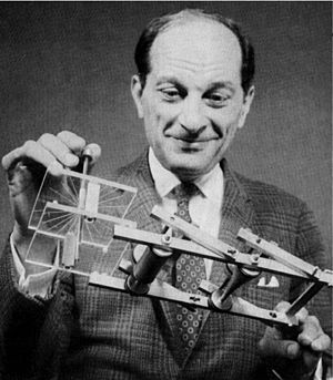 A smiling balding man in a suit and tie holds a strange device that looks like a frame
