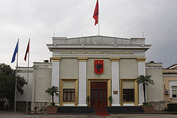 Front of light-colored building with trees, flags and black-on-red Albanian crest