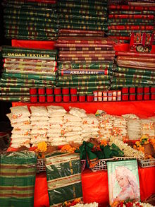 Green and red saris and kumkum on sale in a shop