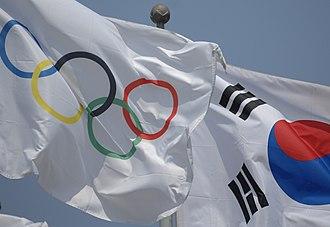 Olympic symbols - Flag of South Korea alongside an Olympic Flag in Olympic Park, Seoul